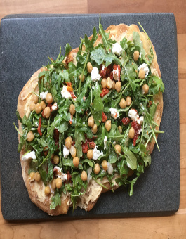 Grilled thin crust pizza with hummus, arugula, sundried tomato, goats cheese and chick peas
