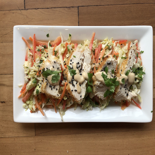 Chicken with tahini sauce over veggie slaw- web